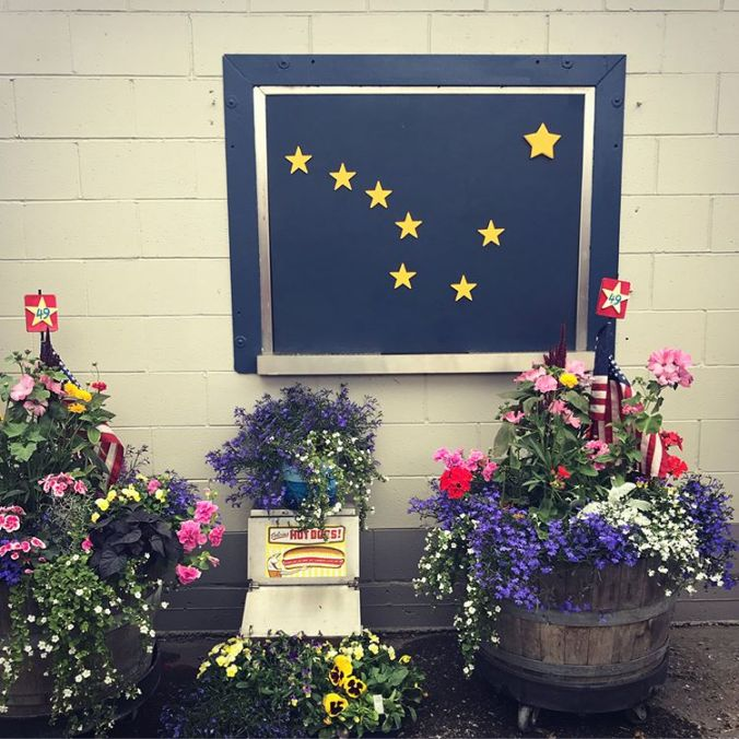 an Alaska flag in front of several pots of flowers