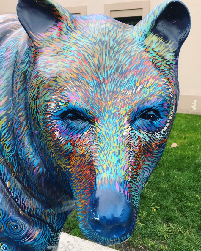 the face of a bear statue painted in many colors