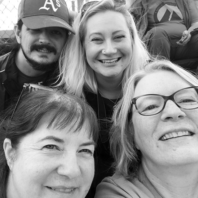 a selfie of four people at a baseball game